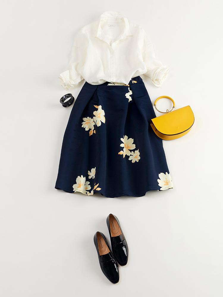 「大人ならではの華やぎ香る深みのあるネイビーベースの花柄スカートに、ホワイトシャツとエナメルシューズを合わせてトラッドなテイストをMIX。鮮やかなイエローバッグでメリハリを添えれば、技あり感も一層高まるはず」(スタイリスト・坂野陽子さん)