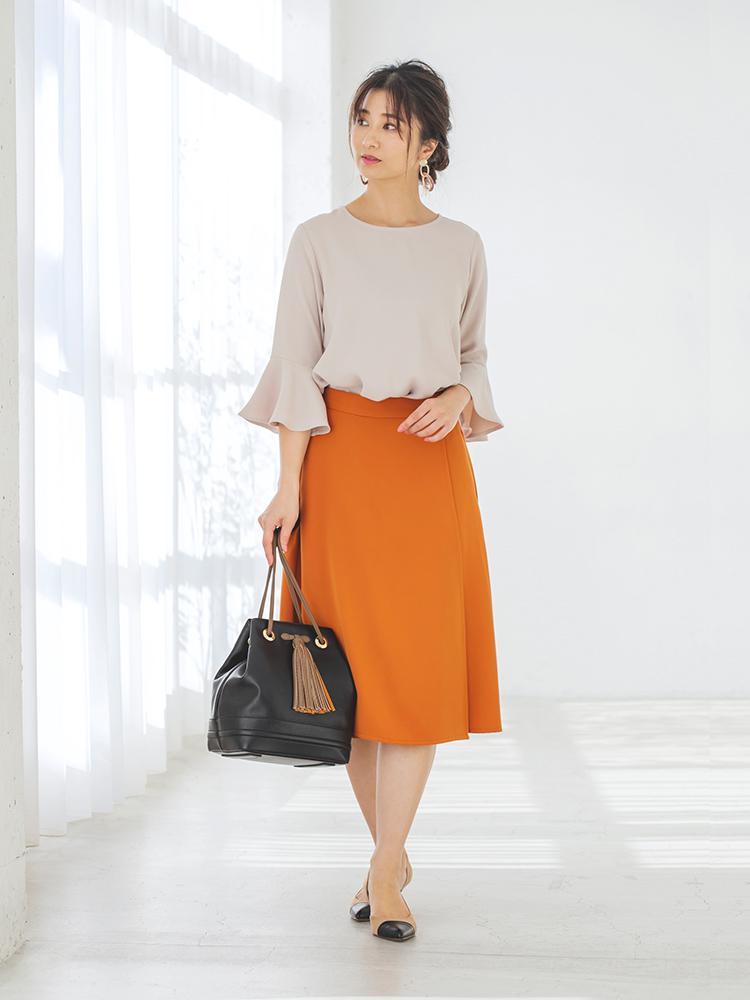 「温かな日差しに映えるオレンジスカートが引き立つよう、ベージュのトップスとパンプス、ダークブラウンのバッグでシック&ソフトに引き算。オフィスにも違和感なくマッチしてくれる秘訣は、柔らかなニュアンスにあり!」(スタイリスト・坂野陽子さん)