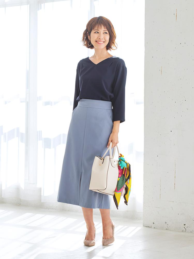 「清潔感のあるネイビーブラウスに、くすみブルーのシックなセミフレアスカートを合わせたシックな着こなしには、ベージュの小物で柔らかなムードをオン。ほんのりと漂う女っぽさで、オフィスでも品の良さを香らせて」(スタイリスト・坂野陽子さん)
