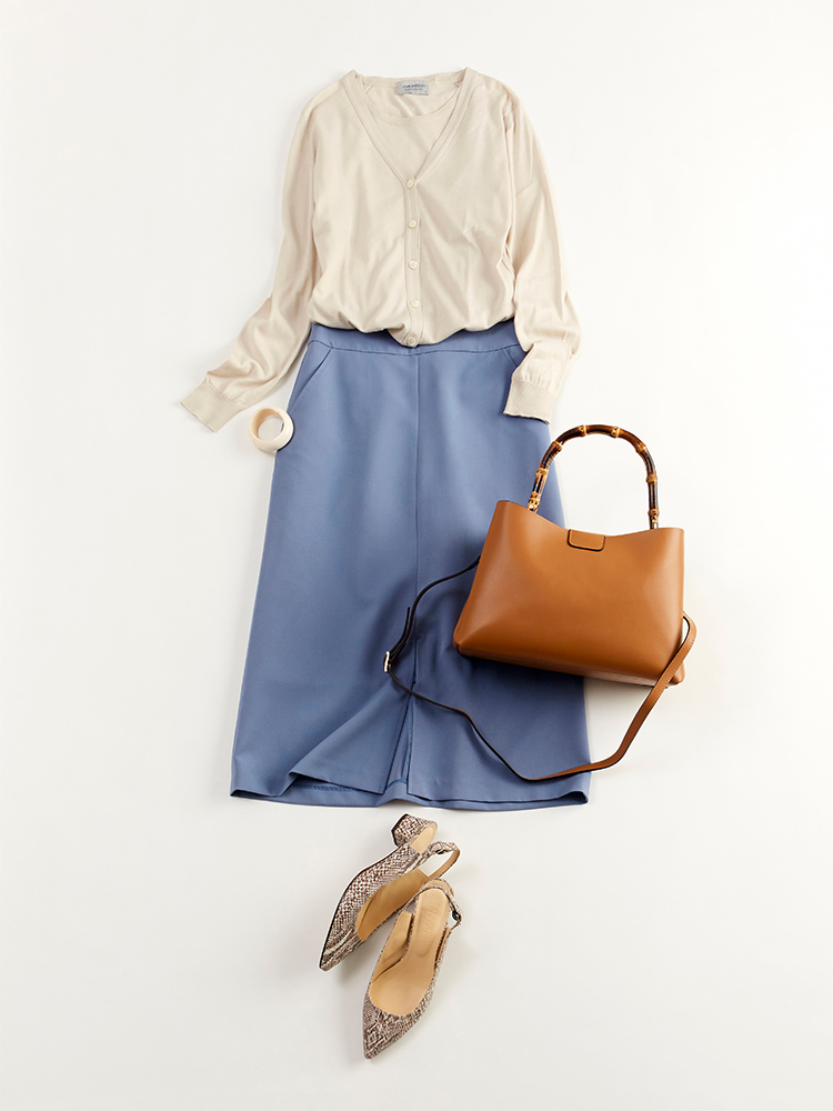 「柔らかなベージュのニットアンサンブルとほんのりくすんだブルーのスカートで、優しげなニュアンスをアピール。大人ならではの気品も忘れないコーディネートは、オフィスでもプライベートでも好印象を与えるはず」(スタイリスト・坂野陽子さん)