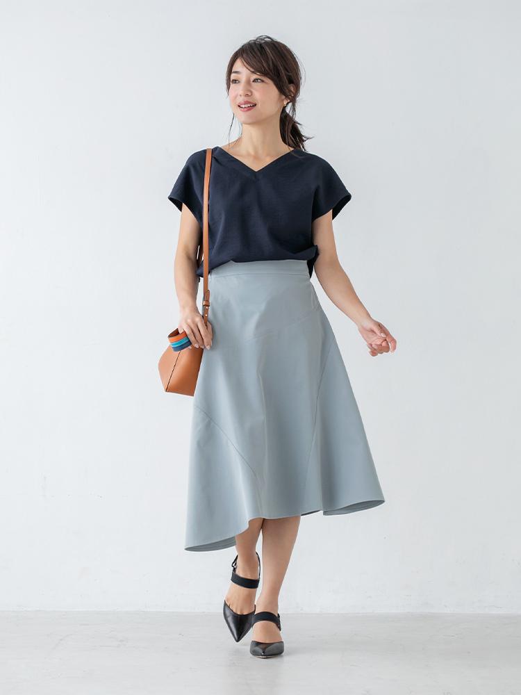 「左右でレングスの異なるアシンメトリーなスカートは、ネイビーのブラウスを合わせたシックな色使いのシンプルコーディネートでもそれとなくモードを主張。いつものオフィススタイルにひとひねりを添えてみて」(スタイリスト・杉本知香さん)