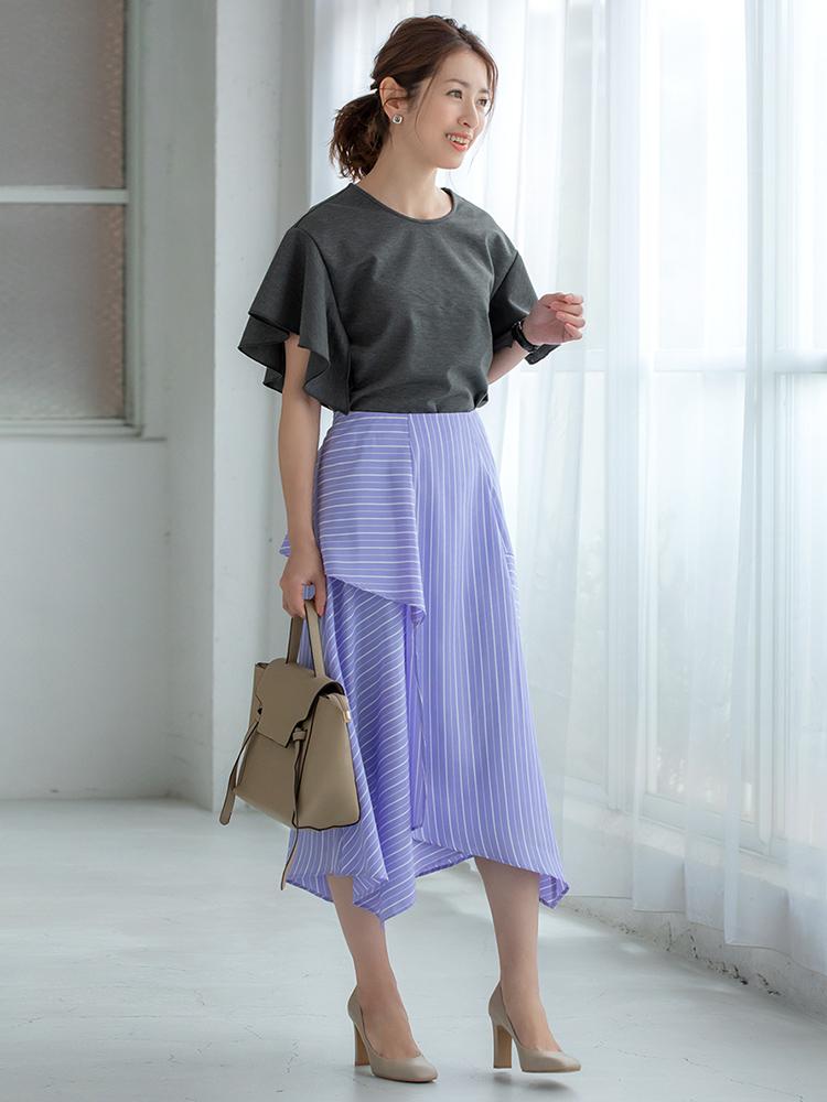 「トップスのフリルスリーブとランダムなスカートの裾で全体的に軽やかでリズミカルな佇まいに。甘くなりすぎないのはグレー〜パープルのカラーリングのおかげ。グレージュ小物で品良くまとめて、ワンランク上の夏のお仕事スタイルへと導きます」(スタイリスト・坂野陽子さん)