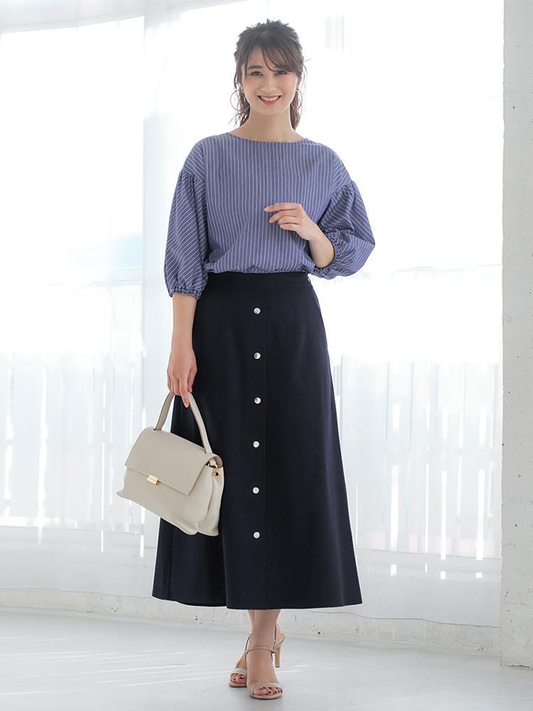「春夏定番のストライプ×ネイビーの安心感のある組み合わせは、トレンド継続のマキシ丈スカートで今っぽくアプローチ。きちんと感のあるバッグでお仕事シーンに相応しいクリーンな印象をはしっかりキープ。足元をスニーカーにすれば、シンプルなのに着映える休日コーデにシフトチェンジ」(スタイリスト・坂野陽子さん)