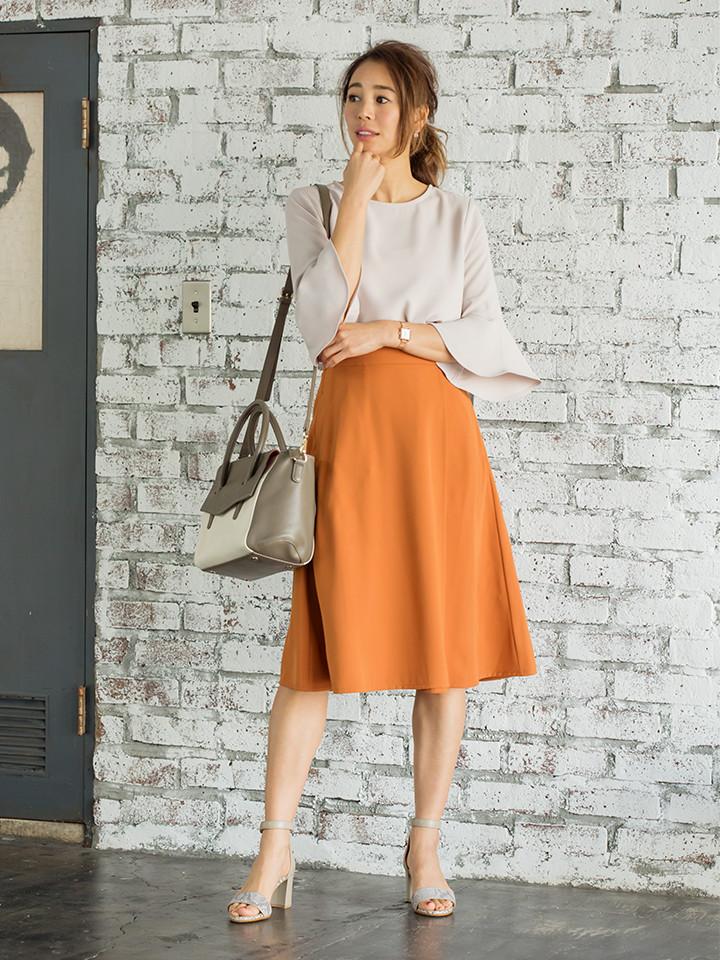 「華やかなオレンジのスカートに淡いベージュ系ブラウスで馴染ませて、全体を柔らかい印象に導いて。お仕事ではパンプス、休日の足元はサンダルでカジュアル感を添えれば、オールシーンにマッチする装いが叶います」(スタイリスト・坂野陽子さん)